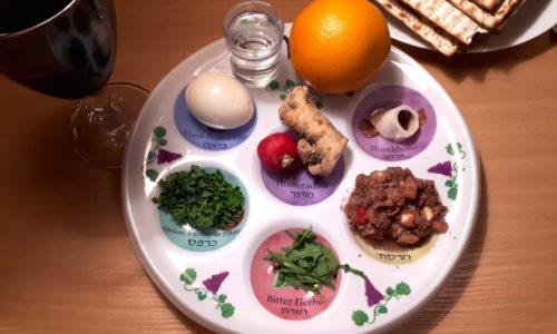 Sederteller mit Matzen und Weinglas.