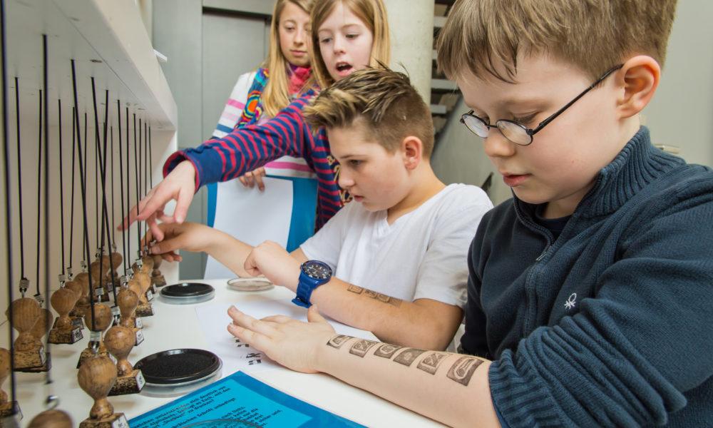 Kinder an der Stempelstation im Jüdischen Museum Franken in Fürth.